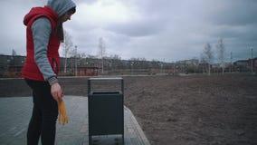 Женщина бросает корку банана в парке сор-ящика публично видеоматериал