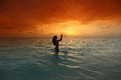 Женщина брызгая в море на заходе солнца Стоковая Фотография RF