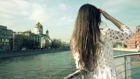 Женщина брюнета в белом платье смотря Христос собор спасителя в Москве сток-видео
