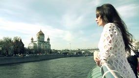 Женщина брюнета в белом платье смотря Христос собор спасителя в Москве видеоматериал
