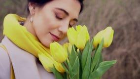 Женщина брюнета в пальто с желтыми тюльпанами акции видеоматериалы
