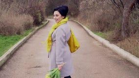 Женщина брюнета в пальто с желтыми тюльпанами видеоматериал