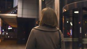 Женщина брюнета идя в город ночи, идущ от работы, проходя торговый центр, назад взгляд видеоматериал