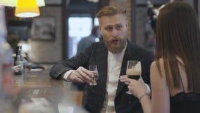 Женщина брюнета и уверенный белокурый бородатый человек сидя на конце счетчика бара вверх Концепция образа жизни ночи r сток-видео
