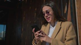 Женщина брюнета открытое сообщение в смартфоне и смеяться, outdoors в солн сток-видео