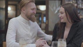 Женщина брюнета очарования и красивый бородатый белокурый человек сидя на таблице Человек говоря добрые слова к его видеоматериал