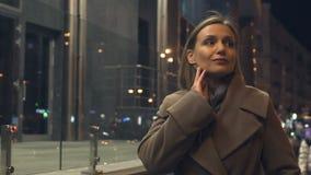 Женщина брюнета привлекательная идя в загоренный город вечером, женственность акции видеоматериалы