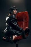 Женщина брюнет в красном кресле стоковое фото