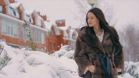 Женщина брюнет в меховой шыбе усмехаясь на предпосылке зданий на улице зимы движение медленное акции видеоматериалы