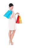 Женщина брюнет в платье creme с представлять хозяйственных сумок Стоковая Фотография RF
