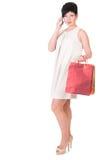 Женщина брюнет в платье creme с представлять хозяйственных сумок Стоковые Изображения