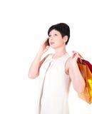 Женщина брюнет в платье creme с представлять хозяйственных сумок Стоковое Изображение