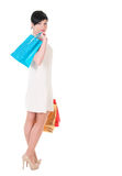 Женщина брюнет в платье creme с представлять хозяйственных сумок Стоковое Изображение RF