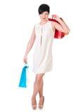 Женщина брюнет в платье creme с представлять хозяйственных сумок Стоковое фото RF