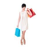 Женщина брюнет в платье creme с представлять хозяйственных сумок Стоковые Фото