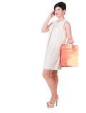 Женщина брюнет в платье creme с представлять хозяйственных сумок Стоковая Фотография