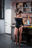 Женщина брюнет в черном бикини представляя в кухне Стоковое фото RF
