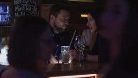 Женщина брюнет говорит с барменом на стойке бара на партии в ночном клубе веселить акции видеоматериалы