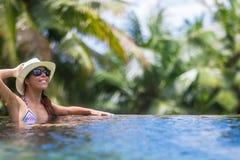 Женщина брюнет детенышей тонкая загорает в тропическом бассейне стоковая фотография