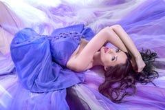 женщина брюнет лежа в длинный фиолетовый лежать платья Стоковое Фото