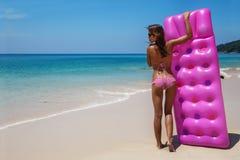 Женщина брюнет детенышей тонкая в солнечных очках загорает на тропическом пляже стоковое изображение rf