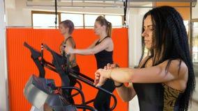 Женщина брюнет используя отслежыватель app фитнеса деятельности на smartwatch пока jogging на третбане сток-видео