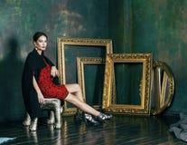 Женщина брюнет красоты богатая в роскошных внутренних близко пустых рамках, нося мода одевает, концепция людей образа жизни стоковое фото rf