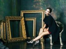 Женщина брюнет красоты богатая в роскошных внутренних близко пустых рамках, Стоковое Изображение