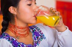 Женщина брюнет крупного плана с красными ожерельем и серьгами, выпивая апельсиновым соком от стекла, закрывая ее наслаждаться гла Стоковая Фотография