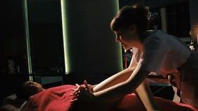 Женщина брюнет лежа на таблице массажа в салоне красоты, пока профессиональный терапевт stomach массаж сток-видео