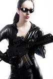 Женщина брюнет молодая сексуальная в латексе с пушкой стоковое фото