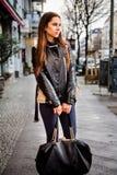 Женщина брюнет нося тяжелую черную сумку стоковые фото