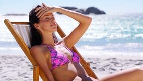 Женщина брюнет ослабляя на шезлонге видеоматериал