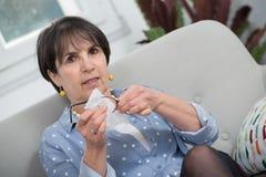 Женщина брюнет очищая ее стекла в софе стоковая фотография rf