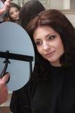Женщина брюнет при новый стиль причёсок смотря зеркало. В парикмахерской. Стоковые Фотографии RF