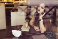 Женщина брюнет сидя на кофе книги чтения кафа, studing и выпивать и говорящ на телефоне Стоковая Фотография