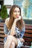 Женщина брюнет спокойная сидя на стенде в улице лета Стоковые Фотографии RF