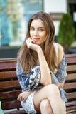 Женщина брюнет спокойная сидя на стенде в улице лета Стоковое Изображение RF
