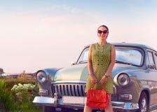 Женщина брюнет стоя около ретро автомобиля стоковое изображение rf