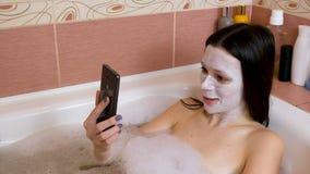 Женщина брюнет с маской на ее стороне лежит в ванной комнате и chattin мобильным телефоном сток-видео