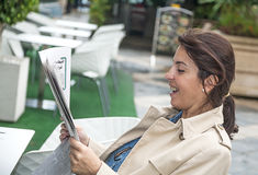 Женщина брюнет читая газету Стоковая Фотография