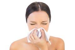 Женщина брюнет чихая в ткани стоковое изображение