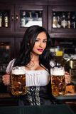 Женщина брюнет Oktoberfest держа кружки пива в баре Стоковое фото RF