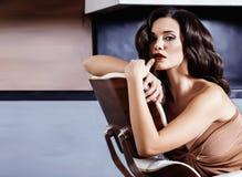 Женщина брюнет yong красоты сидя около камина дома, вечер зимы теплый в интерьере стоковое изображение