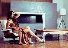 Женщина брюнет yong красоты сидя около камина дома, winte стоковая фотография