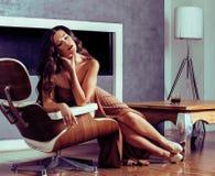 Женщина брюнет yong красоты сидя около камина дома, winte стоковое изображение rf