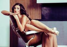 Женщина брюнет yong красоты сидя около камина дома, winte стоковое фото rf