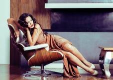Женщина брюнет yong красоты сидя около камина дома, winte стоковые изображения