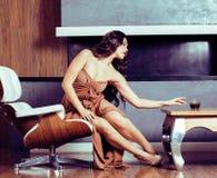 Женщина брюнет yong красоты сидя около камина дома, winte стоковое фото