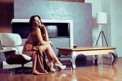 Женщина брюнет yong красоты сидя около камина дома, winte стоковые фото